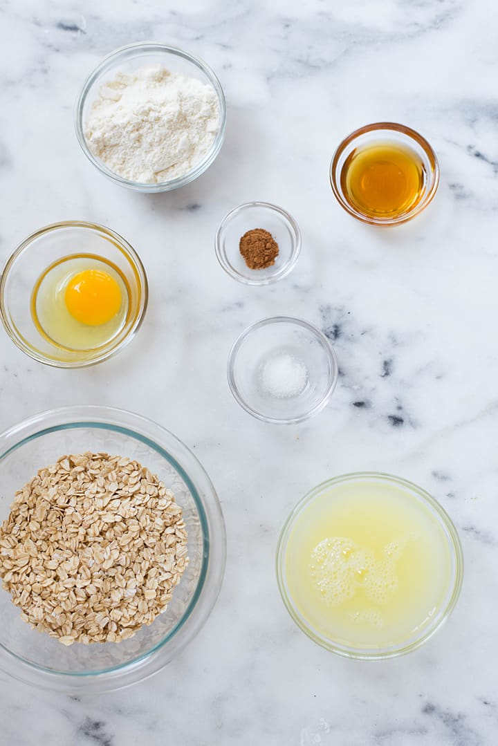 An overhead image of a kitchen counter with all the ingredients for the Oatmeal Protein Pancakes including an egg, protein powder, uncooked rolled oats, pure maple syrup and ground cinnamon.