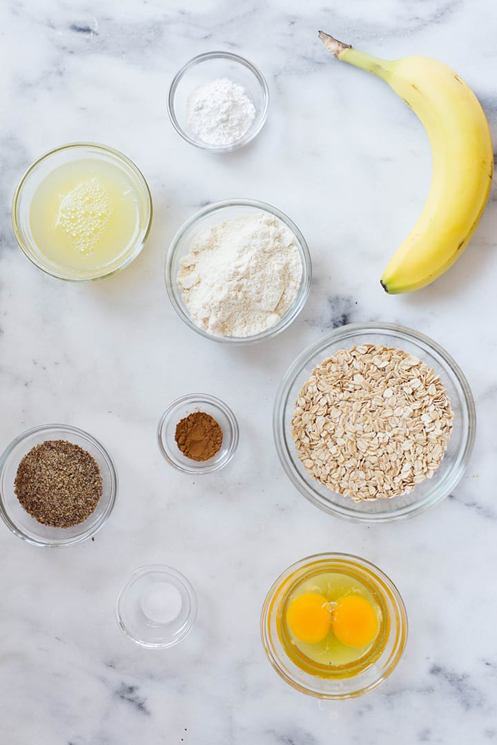 An overhead image of a kitchen counter with all the ingredients for the Banana Protein Pancakes including uncooked rolled oats, a ripe banana, eggs, egg whites, baking powder, sea salt, ground cinnamon, vanilla or unflavored protein powder and ground flaxseeds.