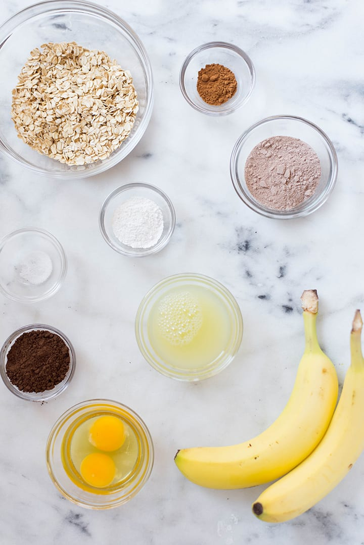 An overhead image of a kitchen counter with all the ingredients for the Chocolate Protein Pancakes including eggs, bananas, uncooked rolled oats, chocolate protein powder, unsweetened cocoa powder and ground cinnamon.