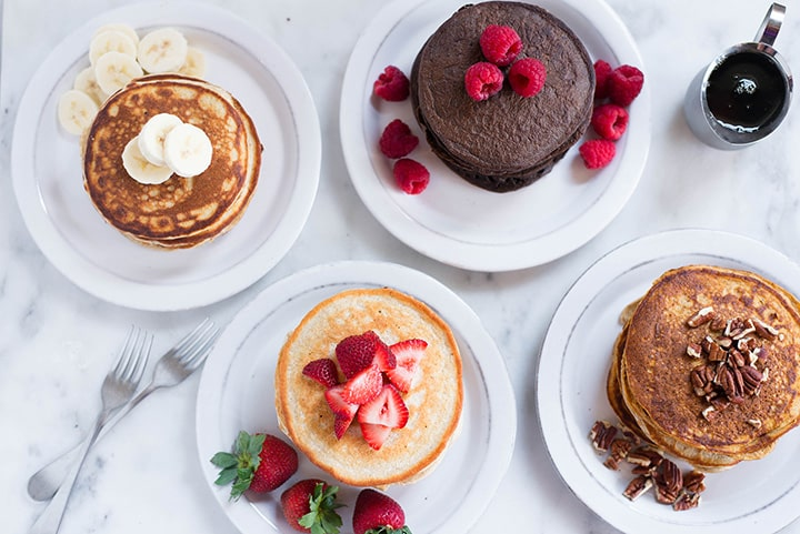 An overhead image of a kitchen counter with 4 different kinds of Protein Pancakes, including Banana Protein Pancakes, Chocolate Protein Pancakes, Sweet Potato Protein Pancakes and Oatmeal Protein Pancakes.