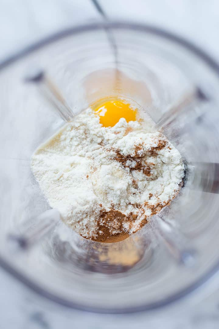 An overhead image of a blender with all the ingredients for the Oatmeal Protein Pancakes ready to be blended, including eggs, uncooked rolled oats, protein powder, pure maple syrup and ground cinnamon.