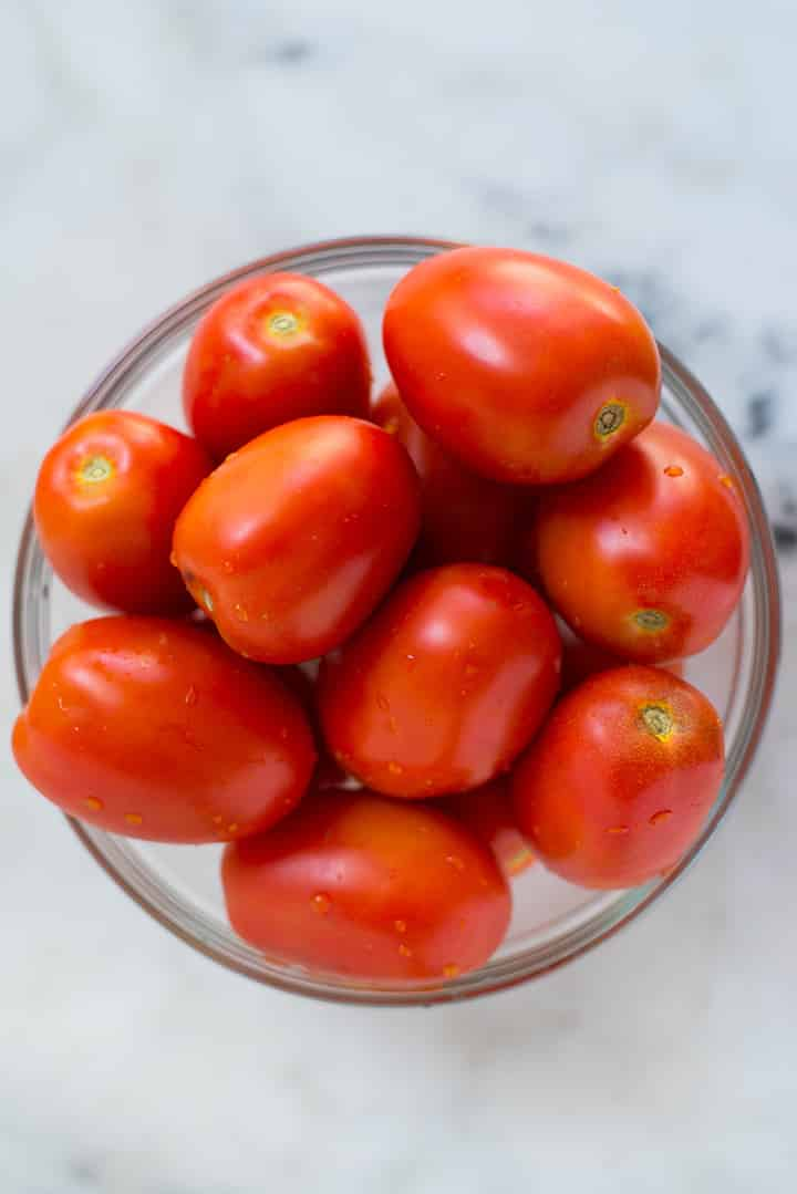 An overhead image of a large glass bowl with fresh roma tomatoes for the Roasted Tomato Sauce.