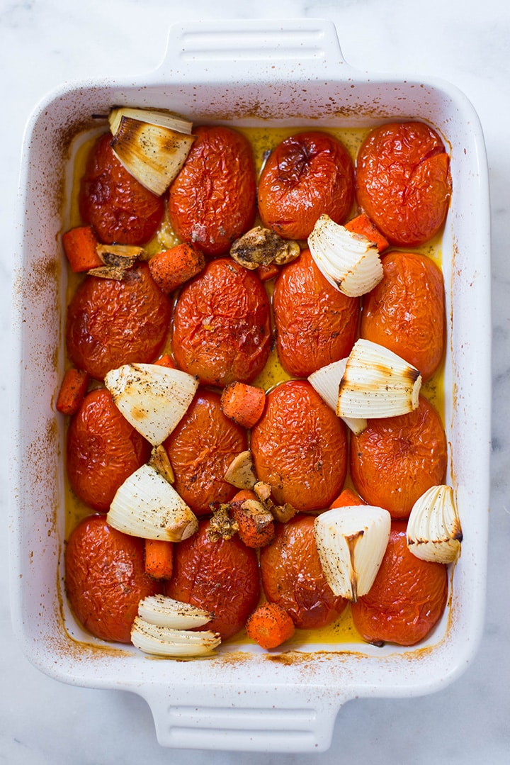 An overhead image of a baking sheet with roma tomatoes, garlic cloves and carrots in olive oil roasted in the oven and ready to be turned into Roasted Tomato Sauce.