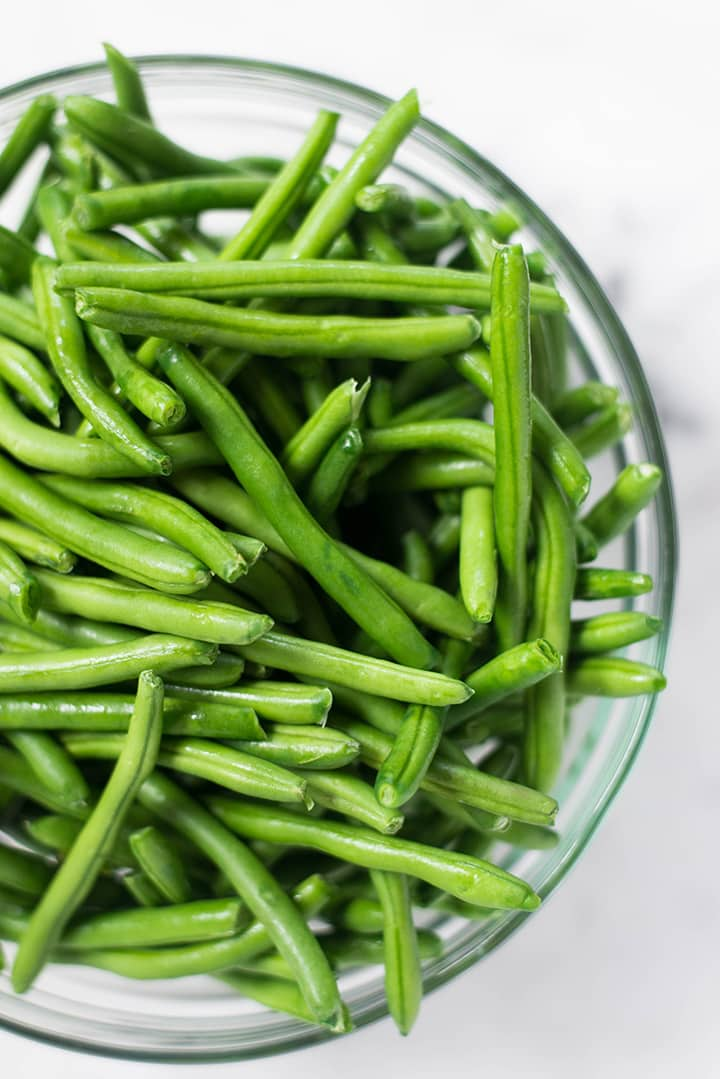 An overhead image of a bowl of fresh green beans for the Southern Green Beans recipe.