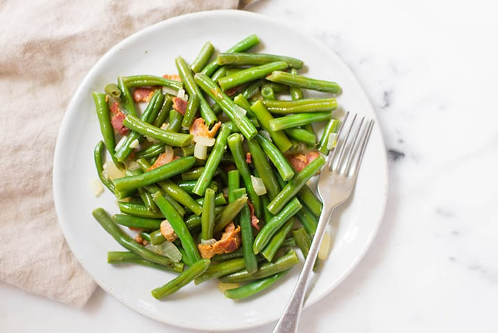 An overhead image of a serving of Southern Green Beans on a plate, made with fresh green beans, cooked bacon, low sodium chicken broth, onion and garlic.
