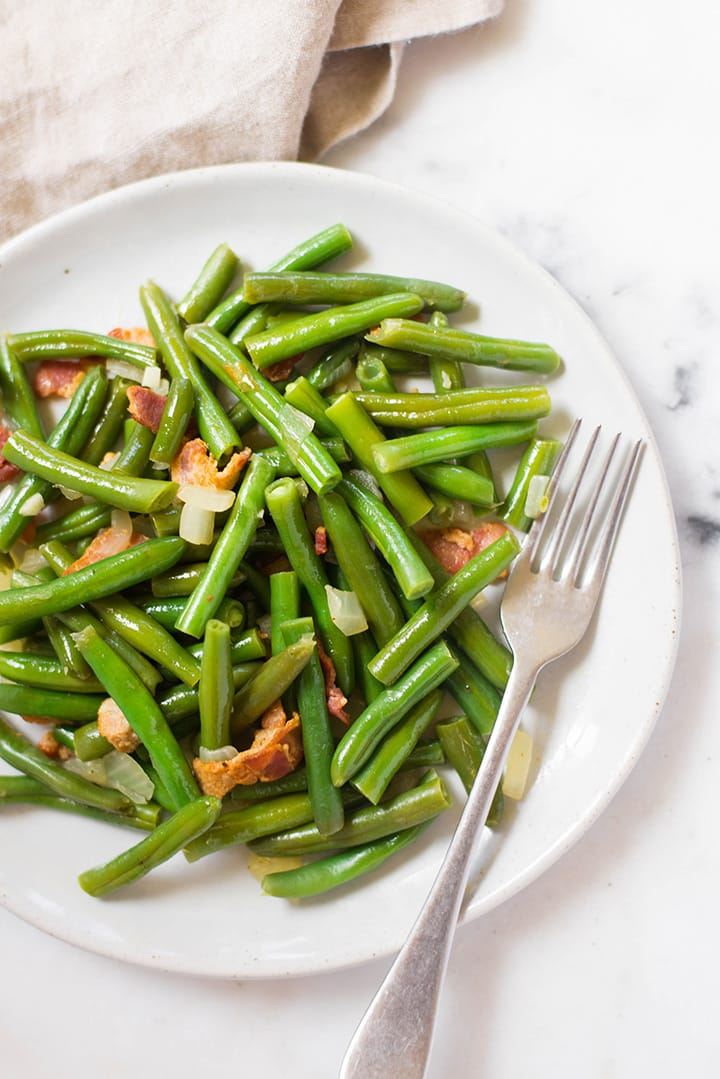 A close up image of a serving of Southern Green Beans, made with fresh green beans, cooked bacon, low sodium chicken broth, onion and garlic.