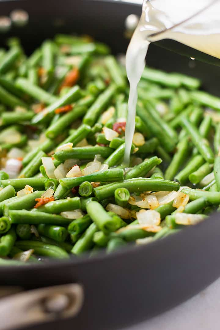 A close up image of pouring the low sodium chicken broth over cooked green beans, cooked bacon, onion and garlic for the Southern Green Beans.