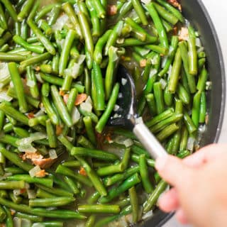 A close up image of a spoon stirring Southern Green Beans made with green beans, cooked bacon, low sodium chicken broth, onion and garlic.