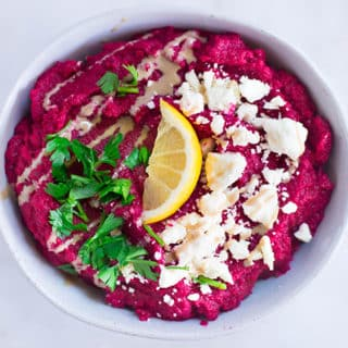 Close up of beet hummus garnished with feta cheese, parsley, and a lemon slice in a serving bowl.
