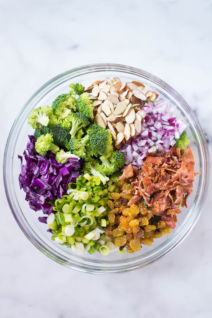 The ingredients for the Healthy Broccoli Salad with Greek Yogurt Dressing including broccoli florets, raising, cabbage, red onion, green onion, bacon crumbles, and almonds in a bowl ready to mix.