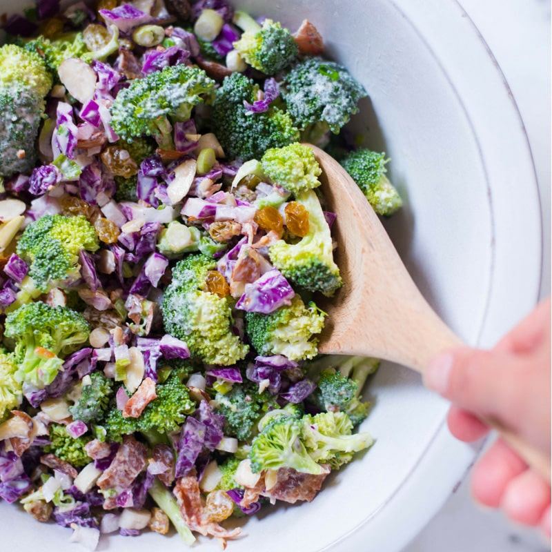 Overhead view of Healthy Broccoli Salad with Greek Yogurt Dressing, including red cabbage, raisins, and almonds.