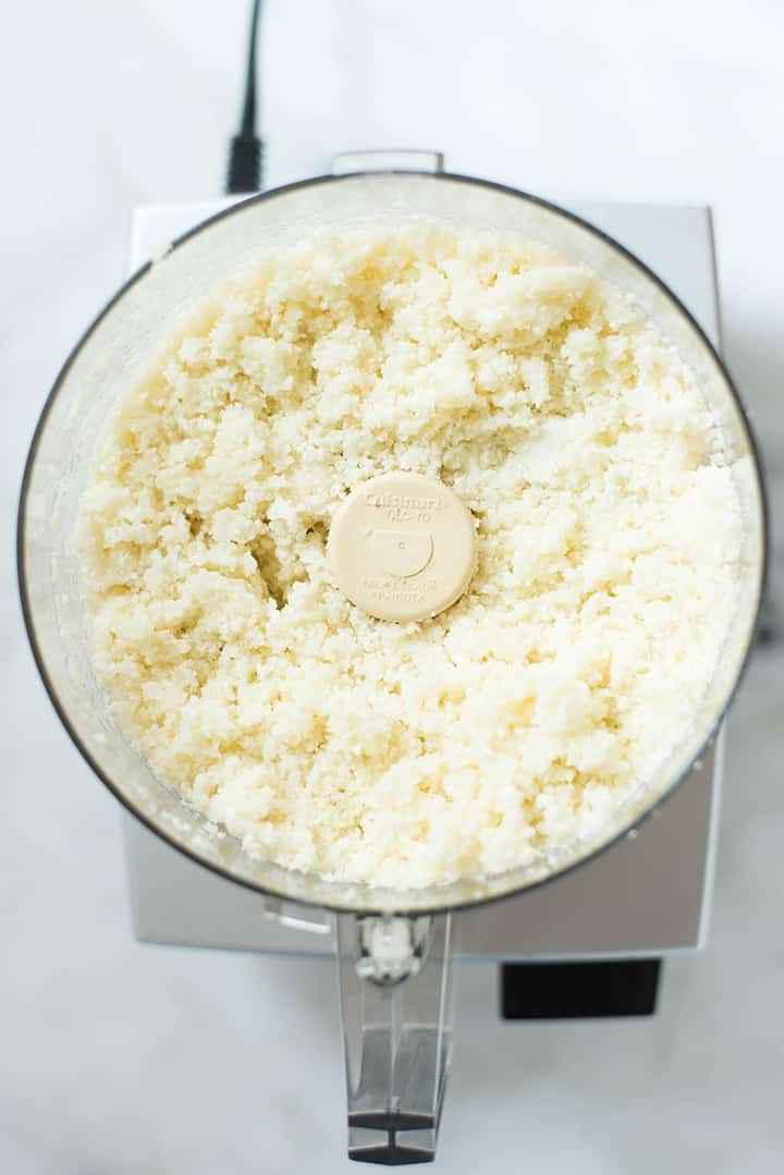 An overhead image of a food processor with processed cauliflower florets for the Cauliflower Tortillas.