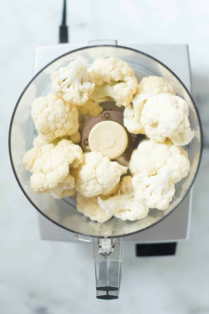 An overhead image of a food processor with cauliflower florets ready to be pulsed for the recipe
