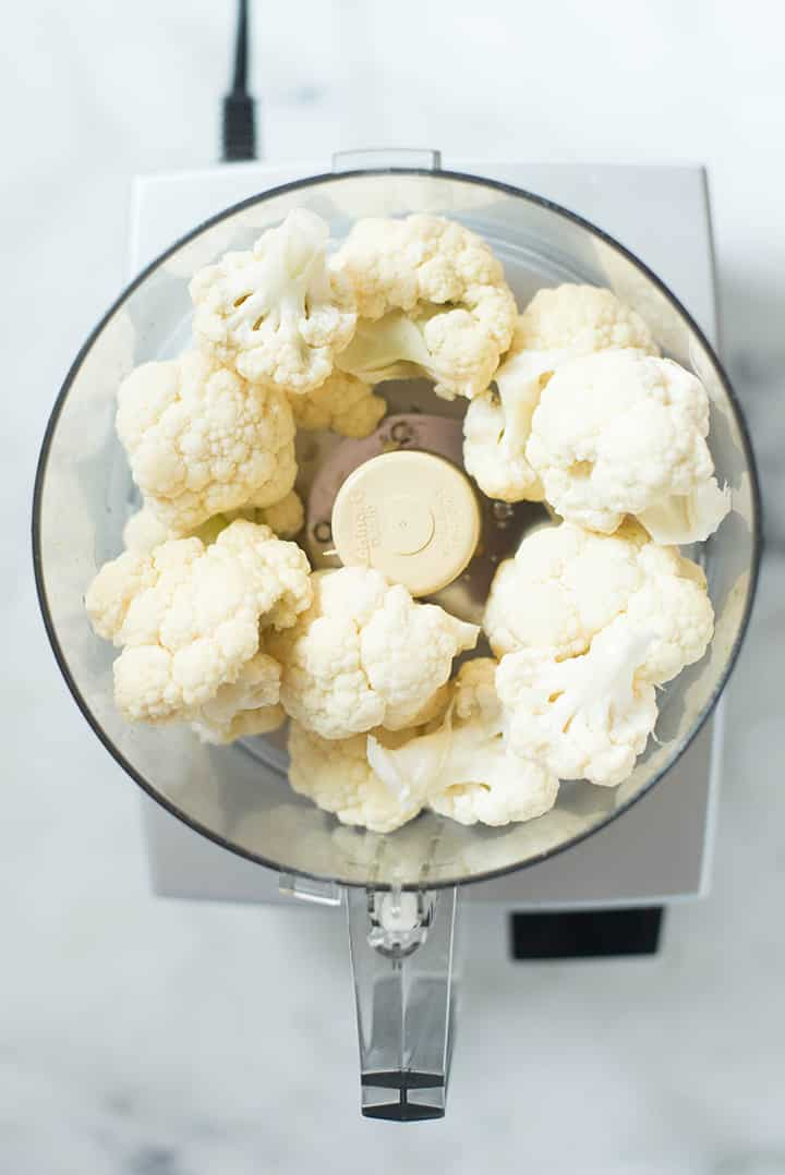 An overhead image of a food processor with cauliflower florets ready to be pulsed for the Cauliflower Tortillas.