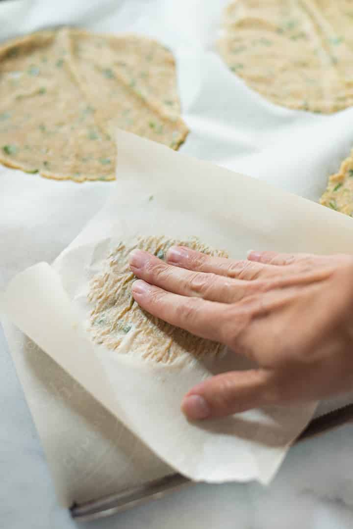 A side image of shaping the Cauliflower Tortillas on a baking sheet by pressing the tortilla mixture with parchment paper into a tortilla shape.