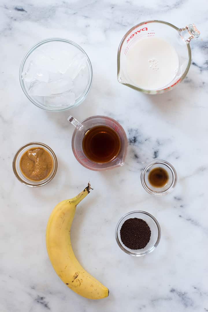 Separated ingredients for the Healthy Coffee Smoothie Recipe including coffee, banana, peanut butter, vanilla extract, and almond milk.