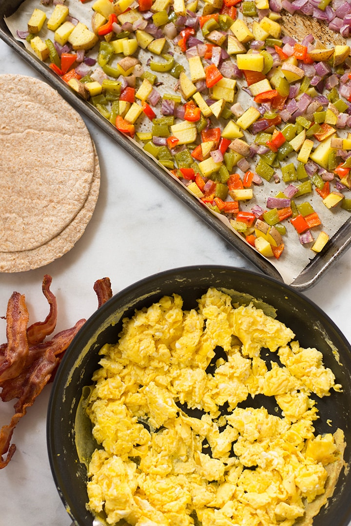Separated ingredients including cheesy scrambled eggs in a skillet, roasted veggies in a tray, whole wheat tortillas, and cooked bacon ready to assemble to make Make Ahead Frozen Breakfast Burritos.