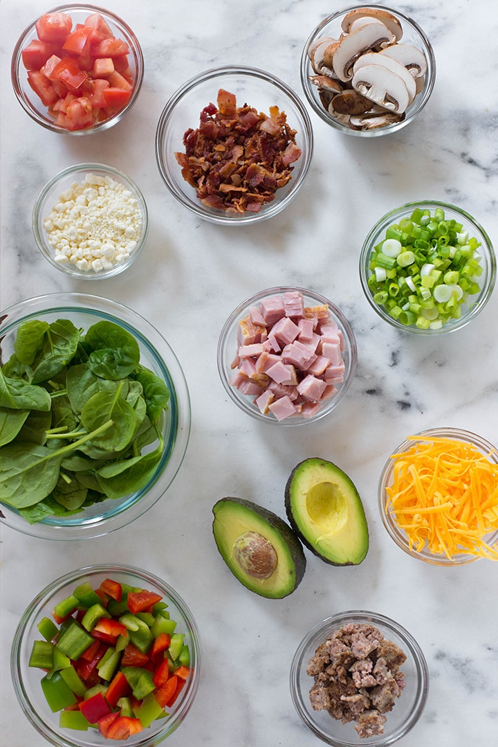 Separated ingredients that can be used in an omelet including ham, avocado, bell pepper, mushrooms, green onion, spinach, shredded cheddar cheese.