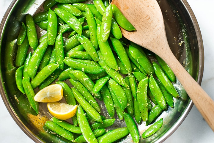 Sauteed sugar snap peas garnished with lemon slices ready to be served.