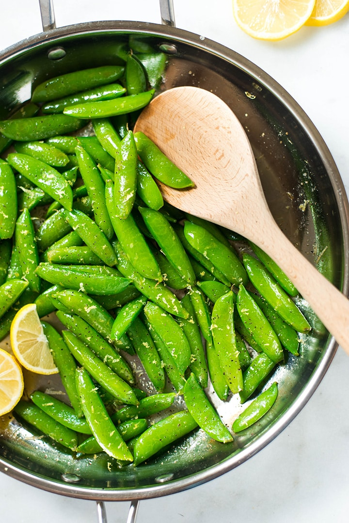 Sugar Snap Peas with Lemon in the pan ready to be transferred to a plate with a wooden spoon. The Sugar Snap Peas were garnished with lemon slices..