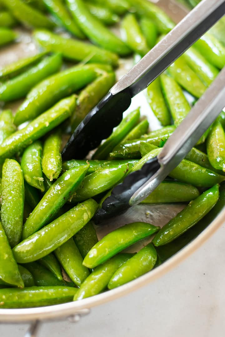 Close up of the sugar snap peas in the pan while being sauteed.