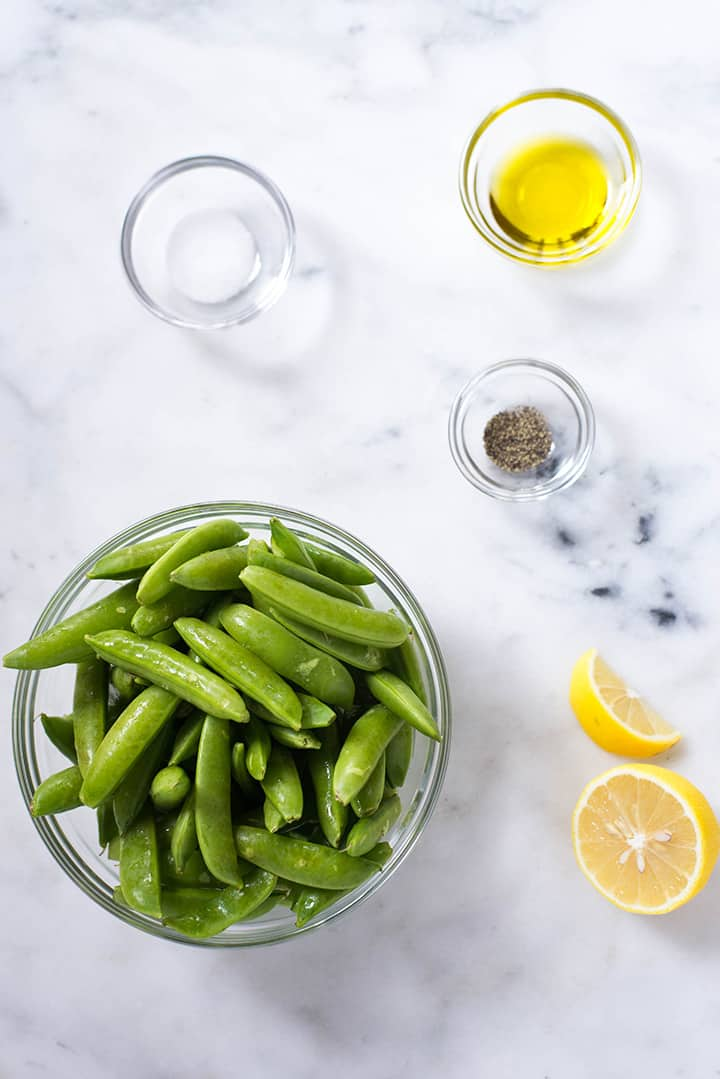 Separated ingredients that will be used to make Sugar Snap Peas with Lemon including sugar snap peas, lemon, olive oil, salt, and pepper.