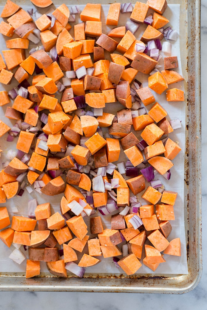 Sweet potato diced into cubes and diced red onion on a baking sheet ready to be put in the oven and transformed into sweet potato hash.