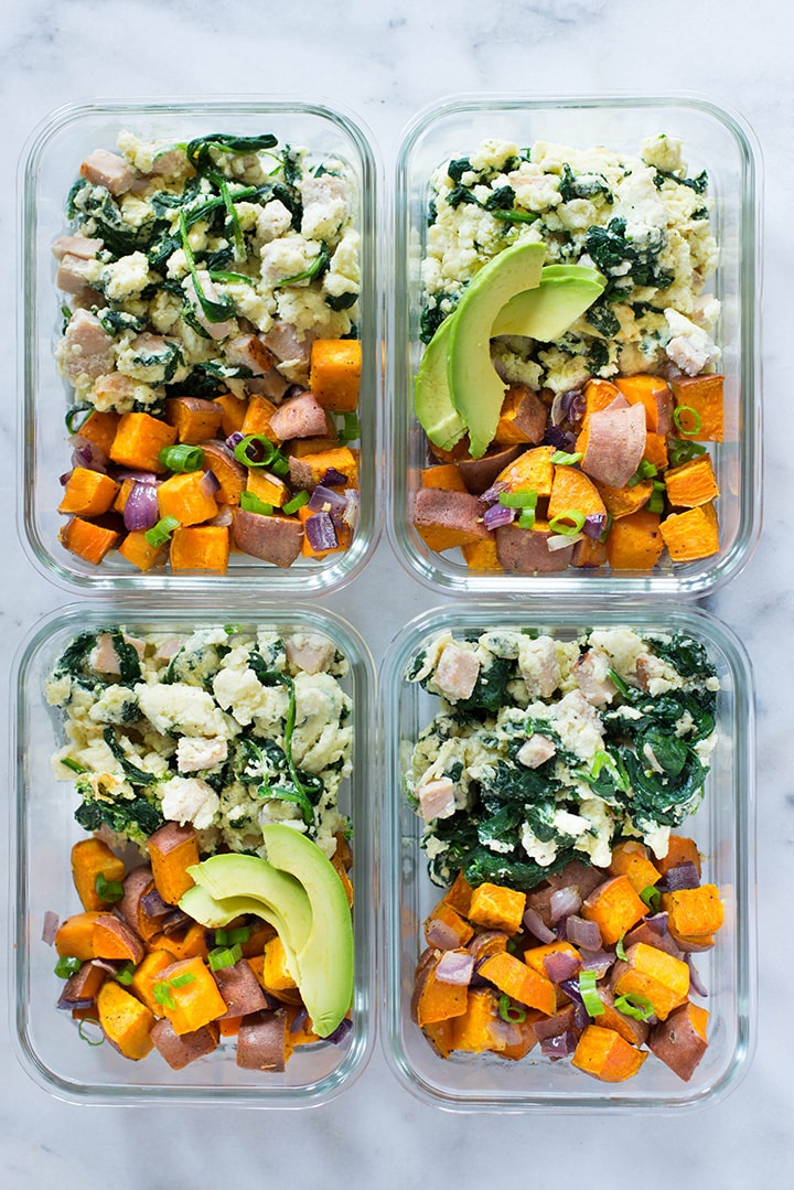 View from above of 4 meal prep containers filled with make ahead breakfast. 2 containers contain only egg whites scramble with ham and spinach & sweet potato has while the other 2 also have a few avocado slices.