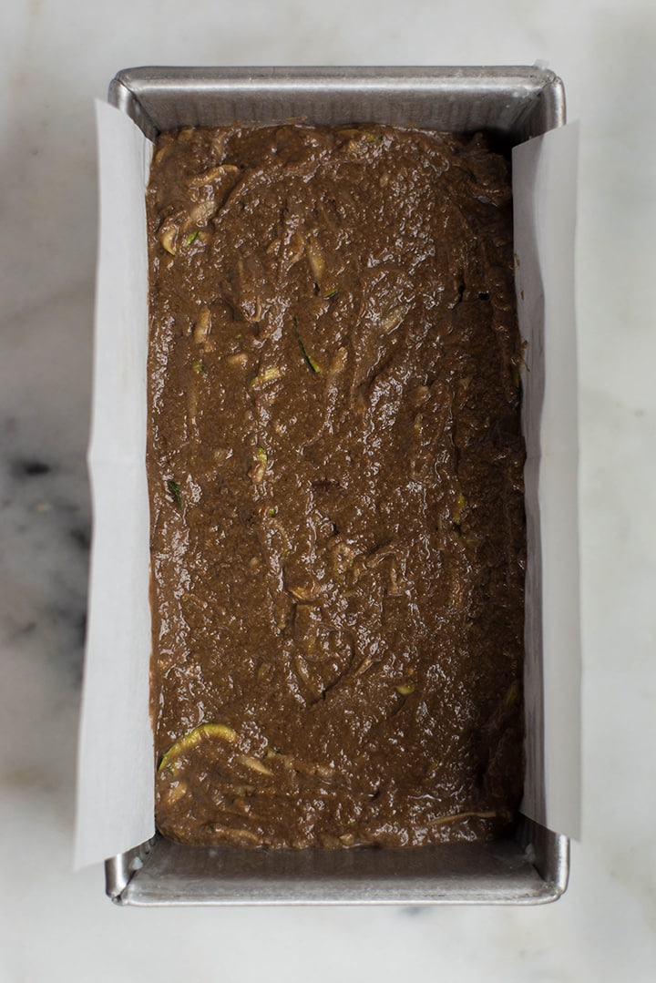 A loaf pan filled with Healthy Chocolate Zucchini Bread mixture ready to be placed in the oven.