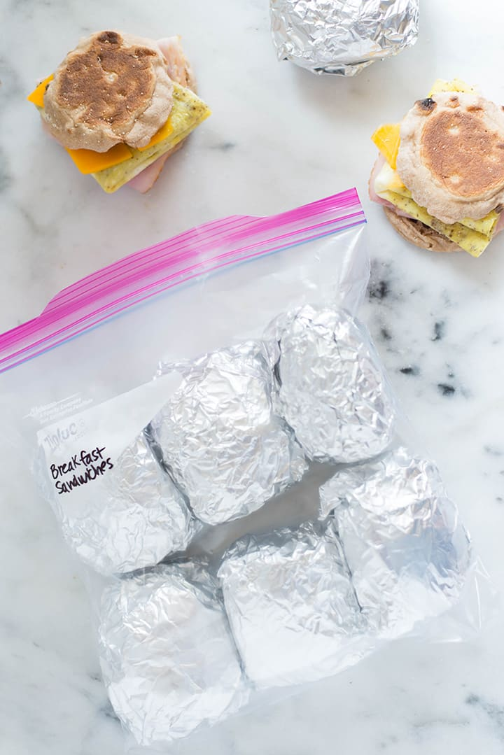 Make-Ahead Freezer Breakfast Sandwiches wraped in plastic foil and aluminum foil placed in a gallon-freezer bag. I the background are other breakfast sandwiches that have to be wrapped in plastic and aluminum foil before being placed in the freezer bag.