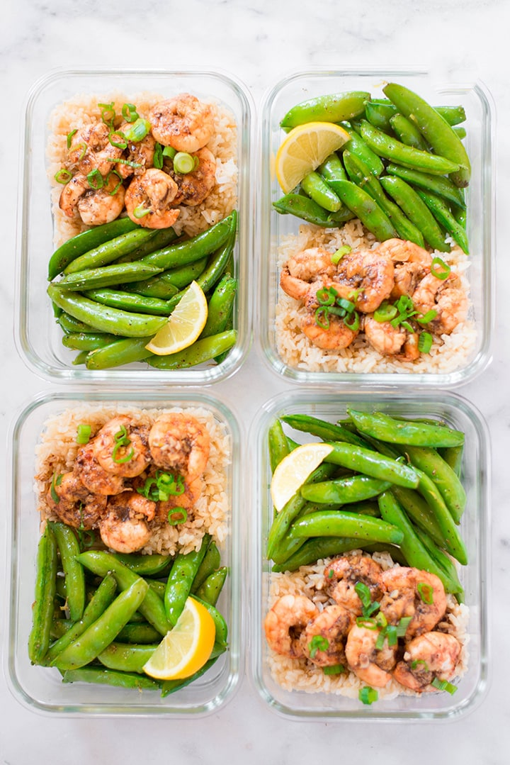 view from above of 4 meal prep containers that contain shrimp, brown rice, sweet peas, and lemon slices.