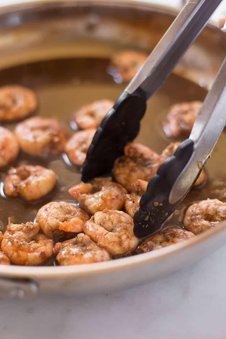 Close up of shrimp being cooked in a pan.
