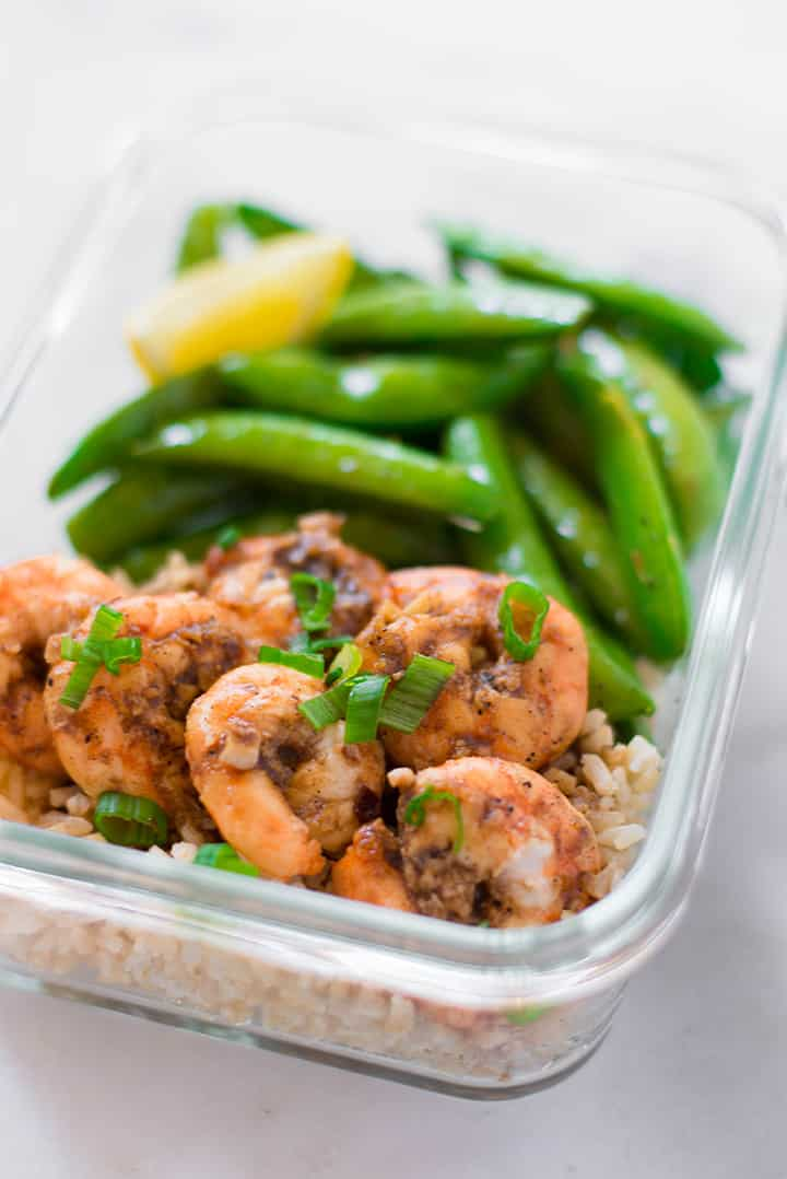Close up of a meal prep container that contains cooked shrimp, cooked rice, cooked sweet peas. The shrimp is garnished with green onions.
