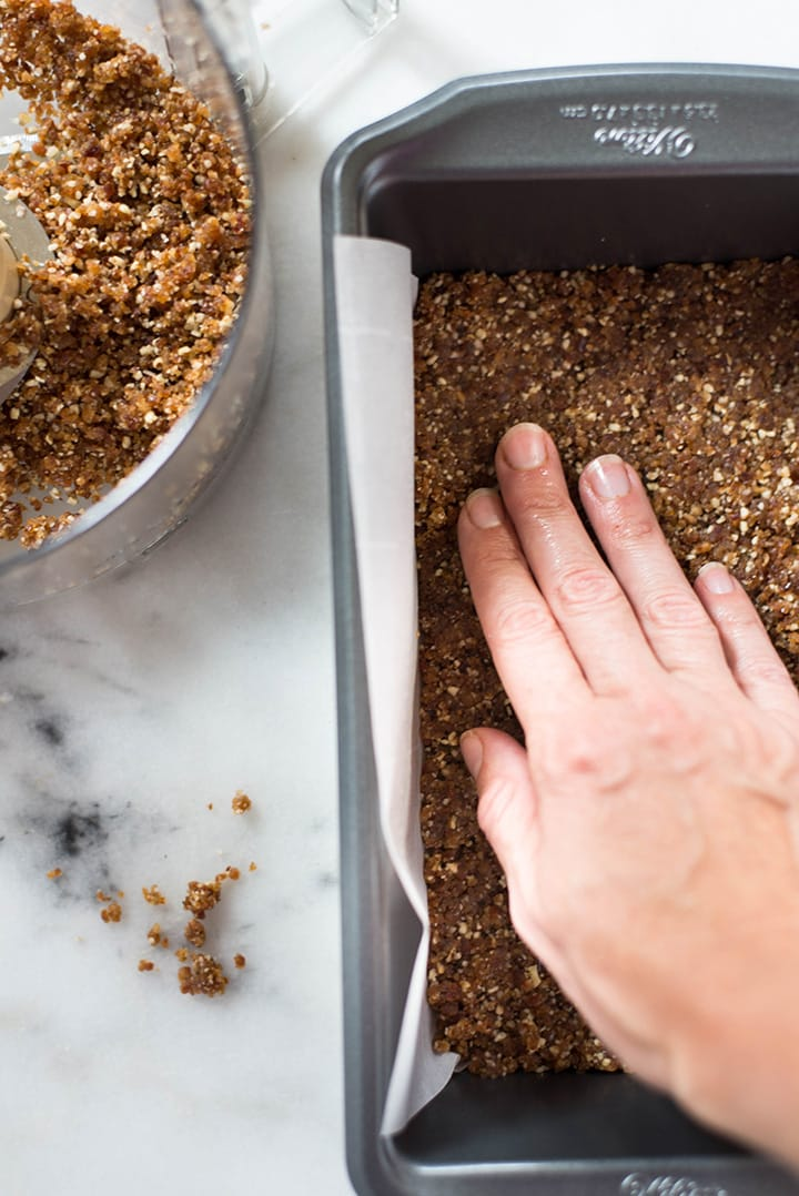 Close up of a hand packing down the cheesecake crust mixture in a loaf pan.