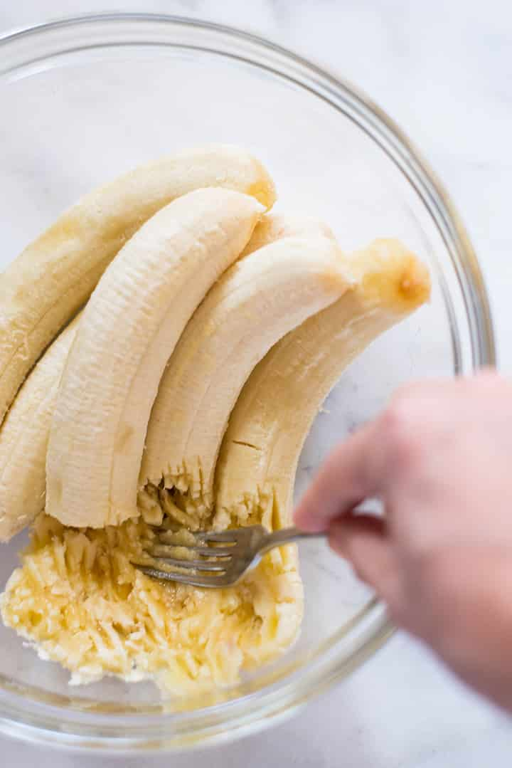 Mashing bananas with a fork in a mixing bowl to make Healthy Banana Nut Bread.