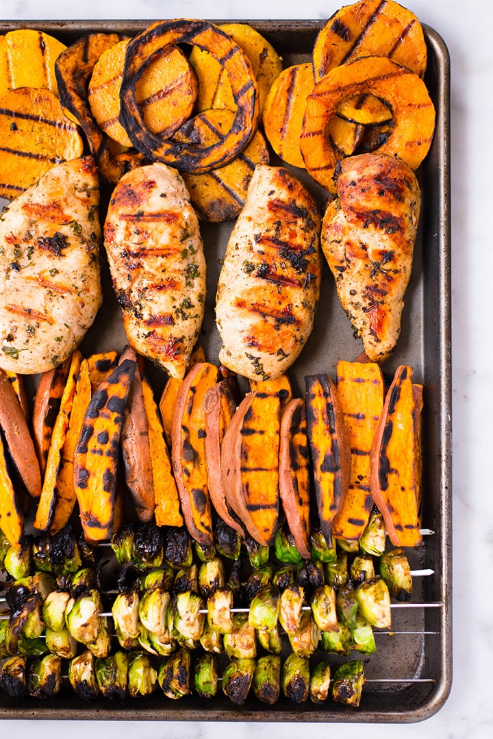 Overhead image of grilled veggies and chicken, placed on a sheet pan ready to serve.
