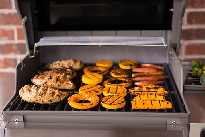 Front view of the chicken butternut squash, and sweet potatoes cooking on the Webber grill.