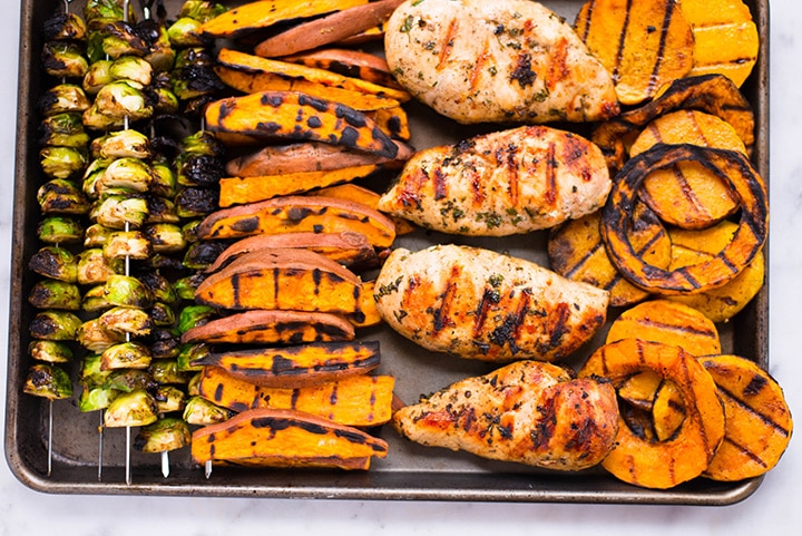 The grilled chicken breasts, grilled butternut quash, grilled sweet potatoes, and grilled Brussel sprouts on a baking sheet.