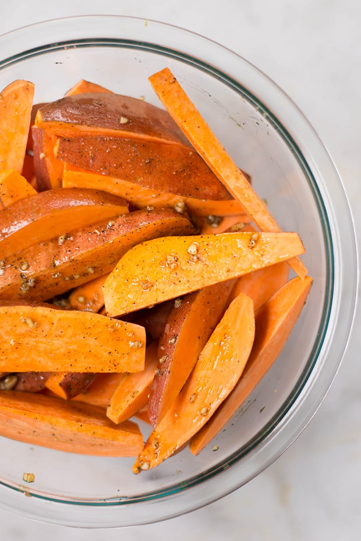 A bowl of sweet potato wedges. The sweet potatoes were tossed with garlic mixture and are ready to be grilled.