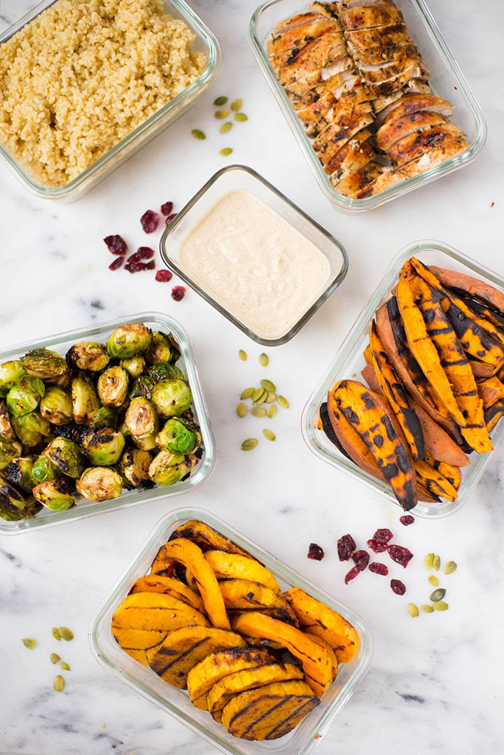The quinoa, grilled sweet potatoes, grilled brussel sprouts, grilled butternut squash, grilled chicken, and Cashew Apple Cider Dressing stored separately in meal prep containers.