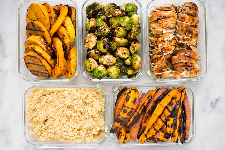 Top view of the Fall Meal Prep on the Grill including grilled chicken, grilled butternut squash, grilled sweet potatoes, grilled Brussel sprouts, and the quinoa base.