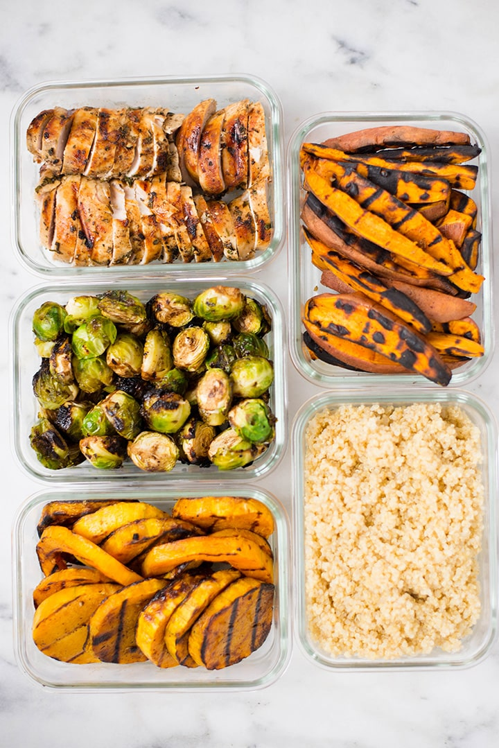 View from the top of grilled chicken, grilled Brussel sprouts, grilled sweet potatoes, grilled butternut squash, and quinoa base stored separately in meal prep containers.