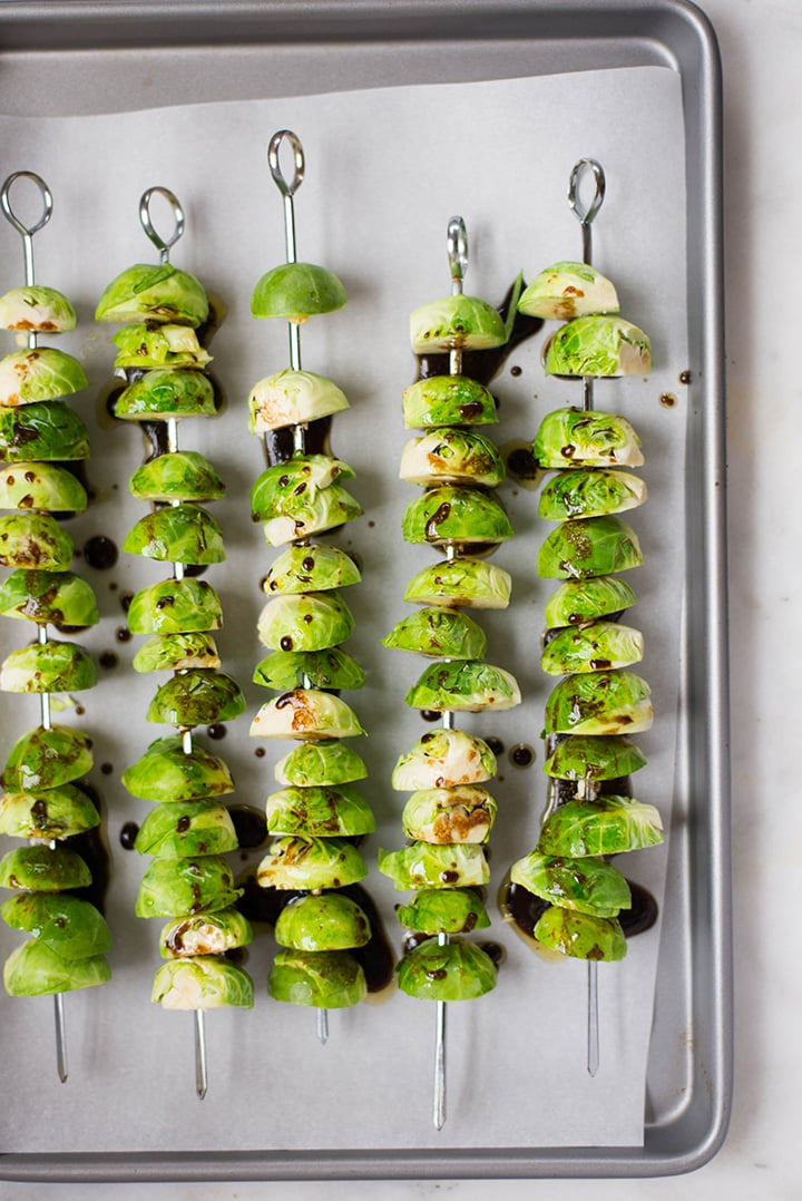 Brussel sprouts skewers drizzled with sweet balsamic sauce.