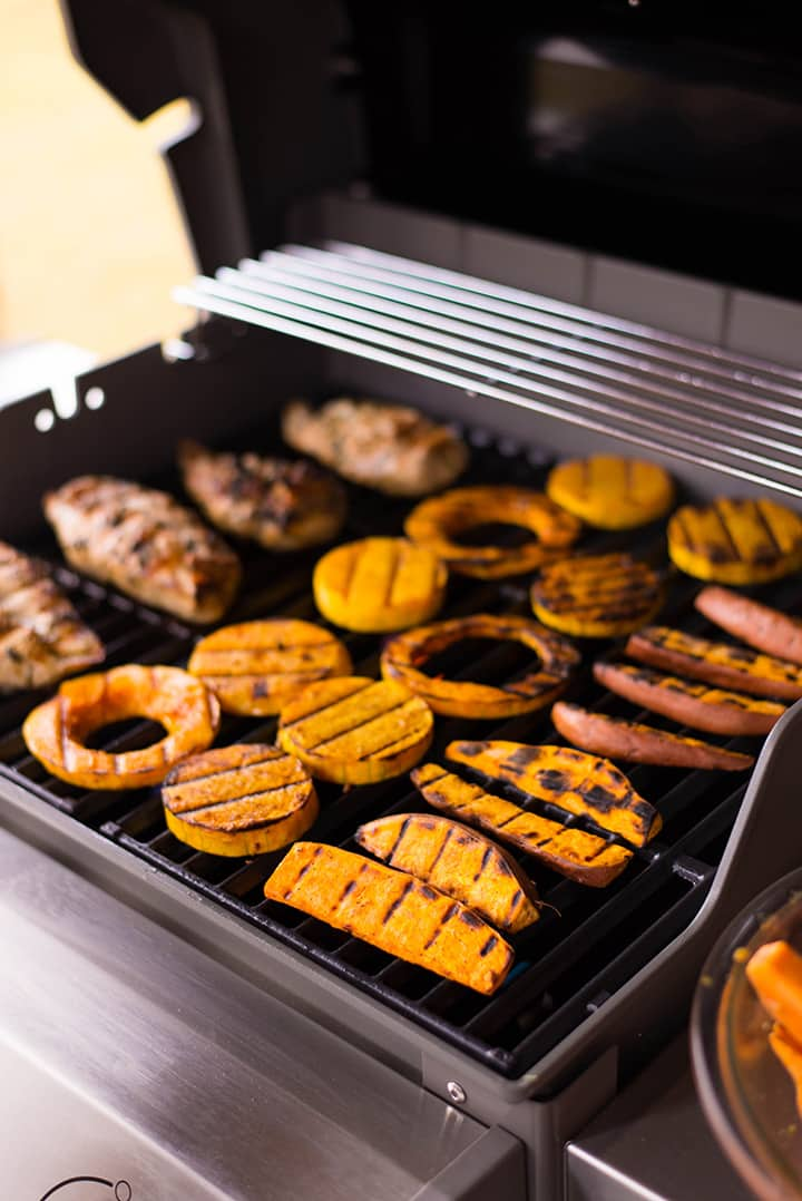 Side vie of the Webber grill with sweet potatoes, butternut squash, and chicken breasts cooking.