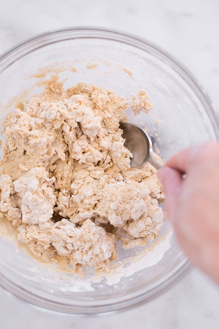 Mixing the ingredients for the whole wheat pizza dough including whole wheat pastry flour, baking powder, sea salt and olive oil in a mixing bowl.