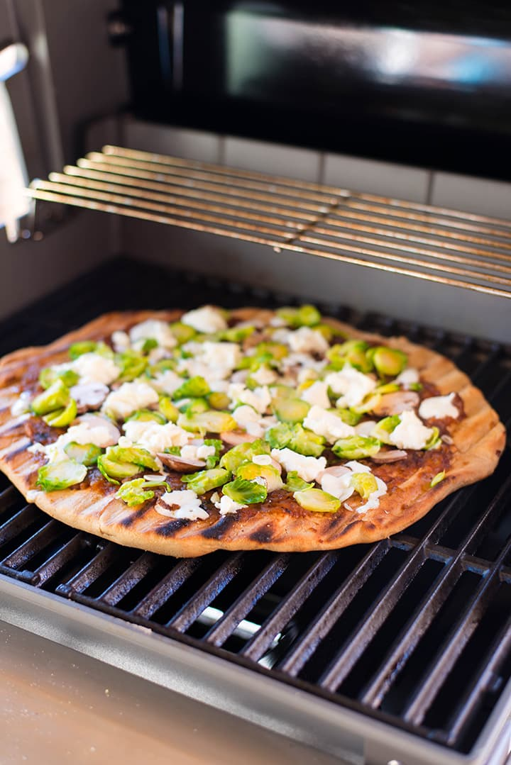 Making grilled pizza with whole wheat pizza crust, maple onion ham Brussel sprouts, mushrooms, ricotta, and mozzarella on the Weber grill.