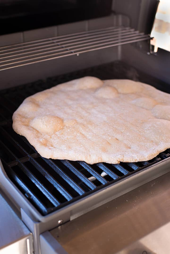 The whole wheat pizza crust cooking on the Weber grill.