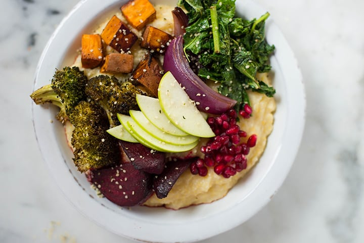 View from the top of the Healthy Harvest Buddha Bowl that contains cauliflower grits, rasted veggies, sauteed kale, slices of apple, and pomegranate seeds.