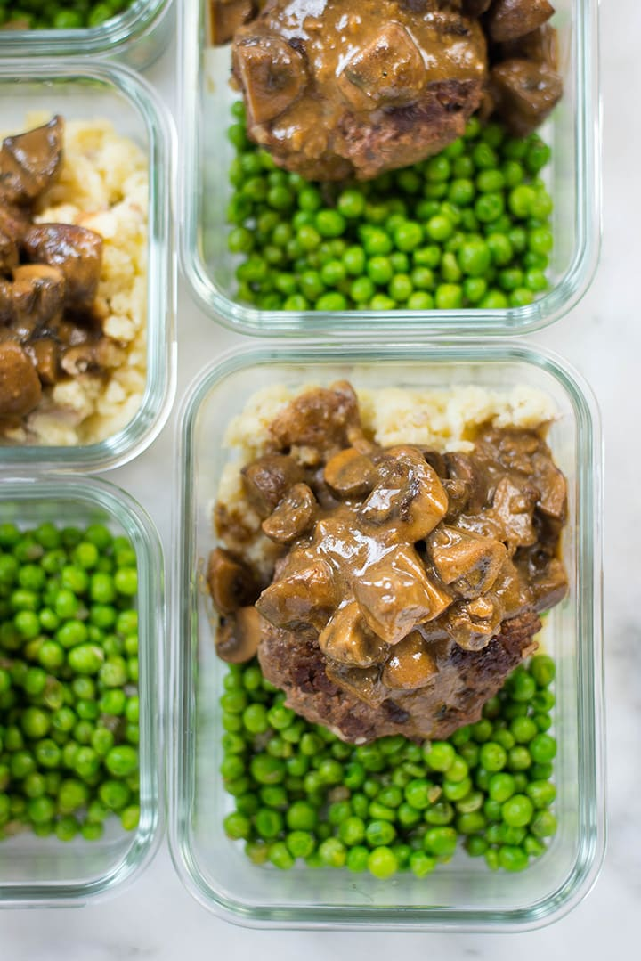 View from the top of the Salisbury steak with peas and potatoes with a close up on one of the meal prep containers.