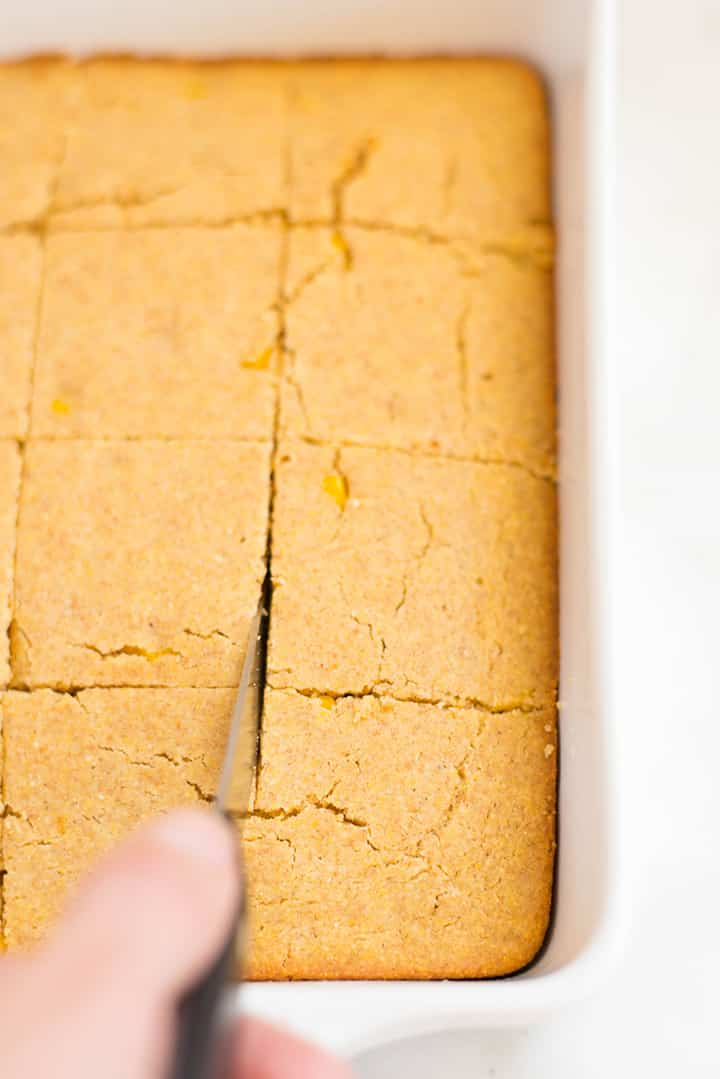 Freshly baked sweet cornbread in the pan being sliced.